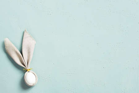Background with Easter egg  decorated with bunny ears of linen napkin on the blue textured table, top view, copy space