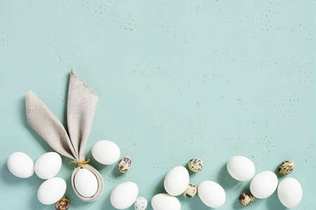 Easter background with chicken and quail eggs with bunny ears of linen napkin on the blue textured table, top view, copy space