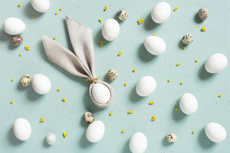 Pattern of chicken and quail eggs with bunny ears of linen napkin, small yellow flowers on the blue textured table, Easter composition, top view Imagens