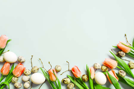Tender Easter background decorated with chicken and quail eggs, coral tulips and tree branches, copy space