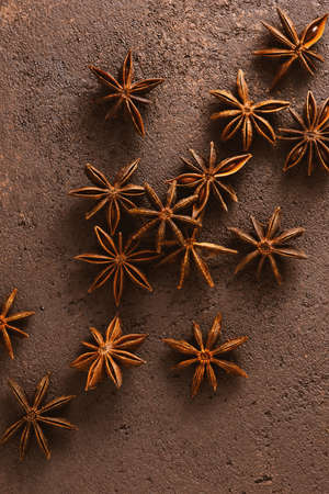 Brown textured background with anise stars, copy space