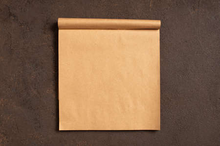 Brown background with blank page of craft sketchbook, top view composition, copy space