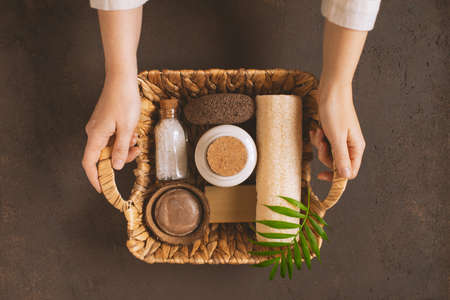 Female hands holding the wicker basket with organic body care products, top view composition