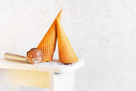 Waffles cones and ice cream ball in the metal spoon on the white background, copy space