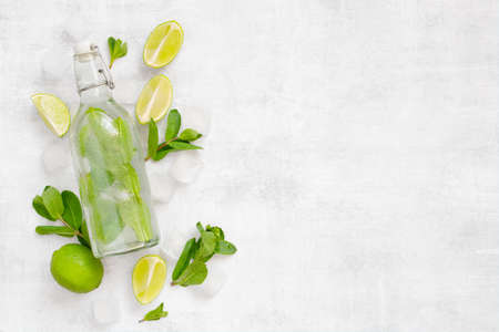 Background with glass bottle with refreshing non-alcoholic mojito on the textured grey table, top view Imagens