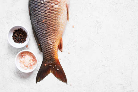 Raw freshwater carp with salt and pepper on the white textured table, copy space