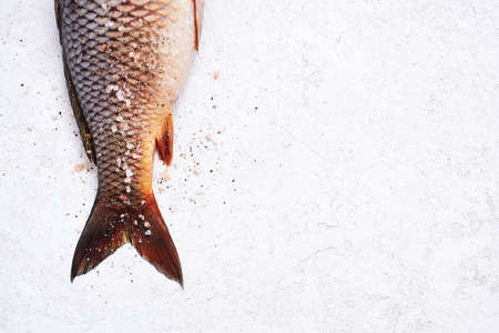 Raw freshwater carp with salt and pepper on the white textured table, copy space Imagens - 120563936