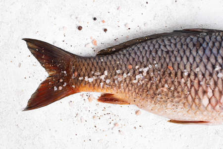 Raw freshwater carp with salt and pepper on the white textured table, top view