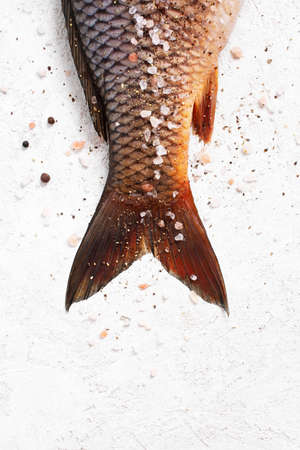 Raw freshwater carp with salt and pepper on the white textured table, top view Imagens - 120563938