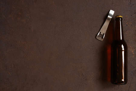 Glass beer bottle and opener on the textured brown table, copy space Imagens - 120563940