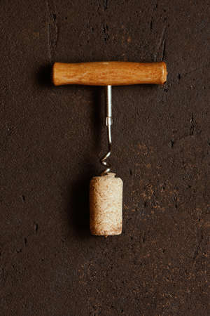 Vintage wooden corkscrew and natural wine cork on the textured brown table, top view Imagens
