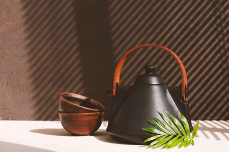 Still life with ceramic teapot and drinking bowls on the table, sunny morning composition