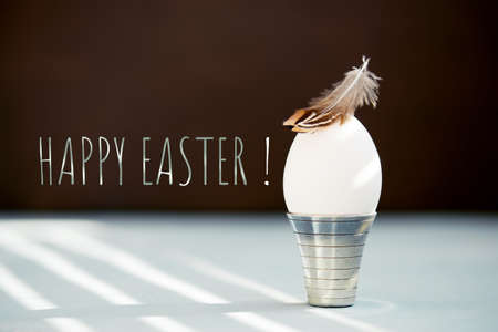 Elegant Easter background with white egg in the stand decorated with small feather, congratulatory text Imagens - 120563943