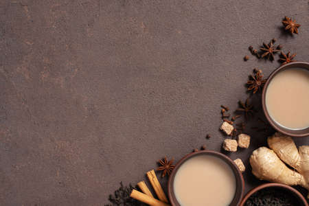 Two cups of spicy Indian masala tea on the brown table, textured brown background Imagens - 120563945