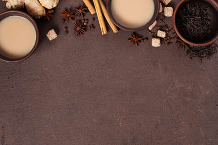 Two cups of spicy Indian masala tea on the brown table, textured brown background