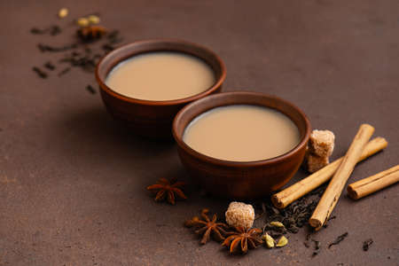 Two cups of spicy Indian masala tea on the brown table Imagens - 120563983
