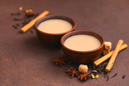 Two cups of spicy Indian masala tea on the brown table