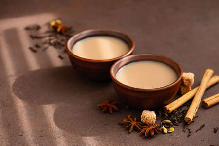 Two cups of spicy Indian masala tea on the brown table, sunny composition Imagens - 120563987