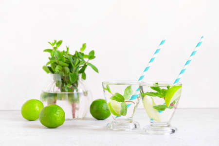 Two glasses of Infusion water or fresh lemonade of lime and mint, refreshing drink on the white table Imagens - 120563988