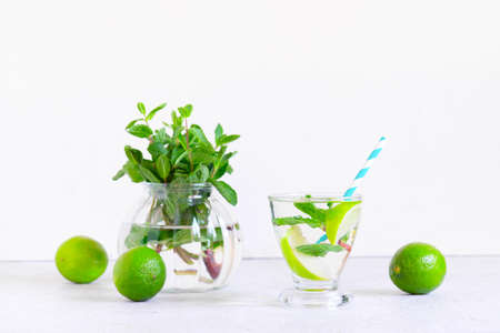Glass of Infusion water or fresh lemonade of lime and mint, refreshing drink on the white table
