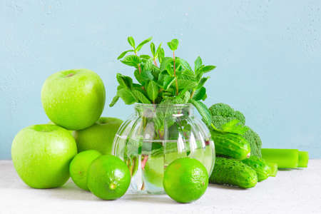 Fresh green vegetables and fruits for healthy eating, ingredients for smoothies or salad on the blue background