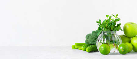 Banner with fresh green vegetables and fruits for healthy eating, ingredients for smoothies or salad on white Imagens