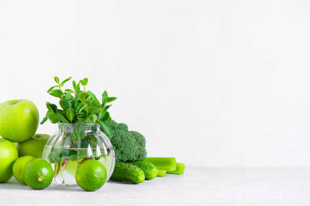 Background with fresh green vegetables and fruits for healthy eating, ingredients for smoothies or salad on white Imagens
