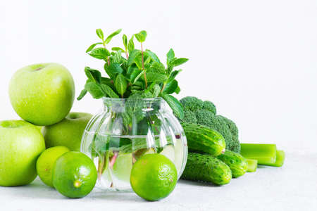 Fresh green vegetables and fruits for healthy eating, ingredients for smoothies or salad on the white background
