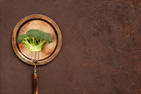 Broccoli on the vintage metal plate on the brown textured table, concept of healthy eating, copy space Imagens
