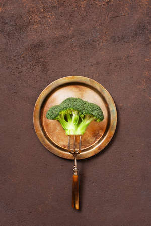 Broccoli on the vintage metal plate on the brown textured table, concept of healthy eating, top view Imagens - 120563997