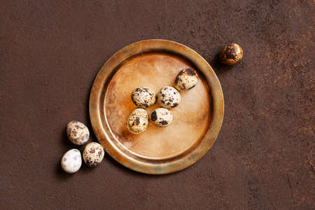 Small natural quail eggs on the vintage brass plate, top view
