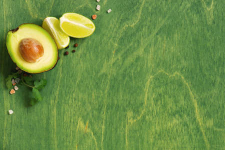 Green wooden background with fresh ripe avocado, lime and seasoning, top  view composition