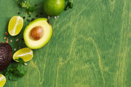 Green wooden background with fresh ripe avocado, lime and seasoning, top  view composition Imagens - 120564050