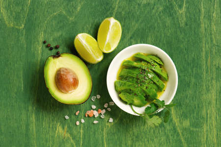 Fresh ripe avocado, lime, olive oil and seasoning on the bright green wooden table, top view composition Imagens