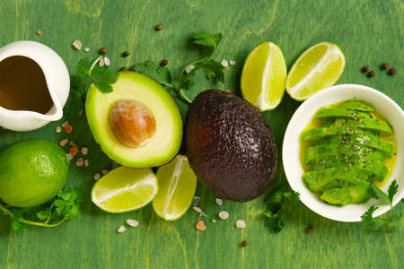 Fresh ripe avocado, lime, olive oil and seasoning on the bright green wooden table, top view composition Imagens - 120564052