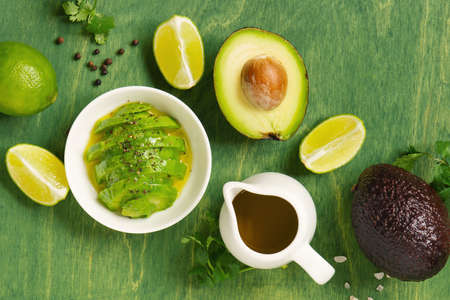 Fresh ripe avocado, lime, olive oil and seasoning on the bright green wooden table, top view composition Imagens - 120564053