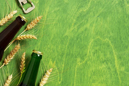 Bright background with beer bottles, opener and ears of wheat on the textured green table, copy space Imagens - 120564055