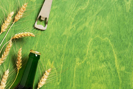 Bright background with beer bottle, opener and ears of wheat on the textured green table, copy space Imagens - 120564056