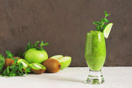 One glass of fresh green fruit smoothie on the table, drink and ingredients for it, brown background Imagens