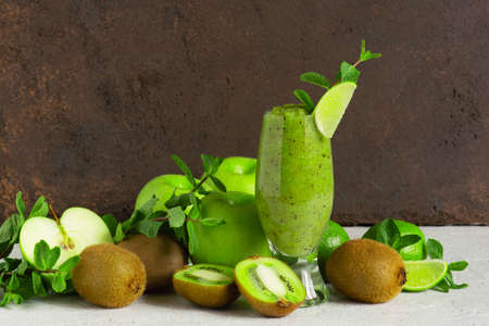 One glass of fresh green fruit smoothie on the table, drink and ingredients for it, brown background Imagens - 120564059