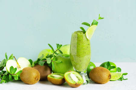 One glass of fresh green fruit smoothie on the table, drink and ingredients for it, blue background