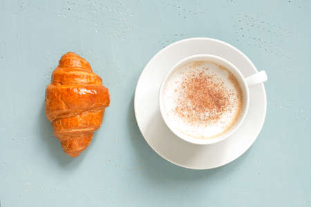 White cup of cappuccino with fresh croissant on the light blue table, top  view Imagens