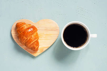 White cup of black coffee with fresh croissant on the light blue table, top view Imagens - 120564065