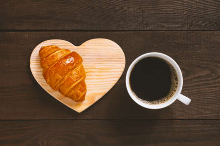 White cup of black coffee with fresh croissant on the brown table, top view