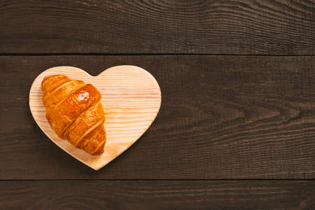 Fresh sweet croissant on the brown wooden table, top view