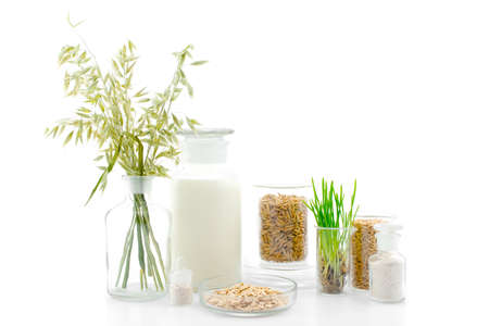 Various products of oat in the medical bottles on white, concept of organic food Stockfoto