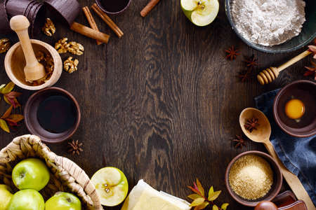 Background with ingredients for traditional apple pie on the textured brown wooden table, top view