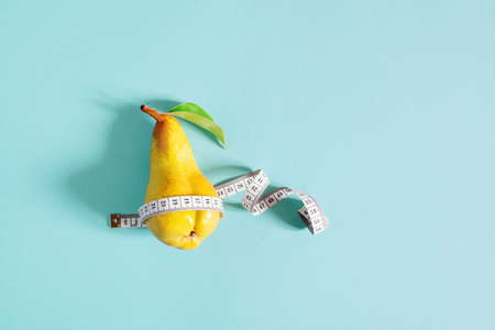 Weight loss concept, yellow pear checks body shapes with measuring tape, blue background