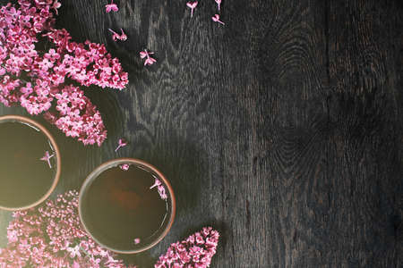 Background with two cups of tea on the dark wooden table decorated with blooming lilac, copy space