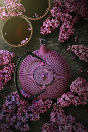 Teapot and two cups of tea on the dark wooden table decorated with blooming lilac, top view